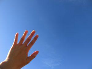女性の手 青空
